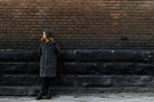 Girl in front of wall with different sized bricks